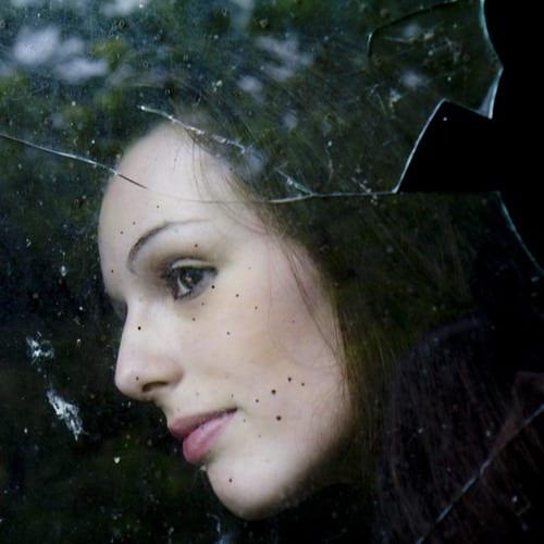 woman looking out broken Houston windows